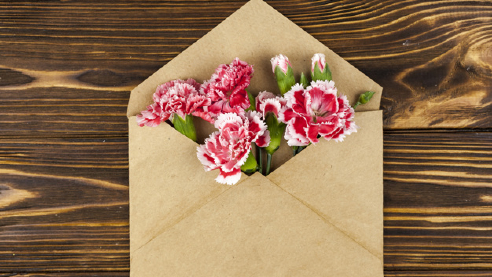 brown-envelope-with-red-carnation-flowers-over-wooden-desk_23-2148058567